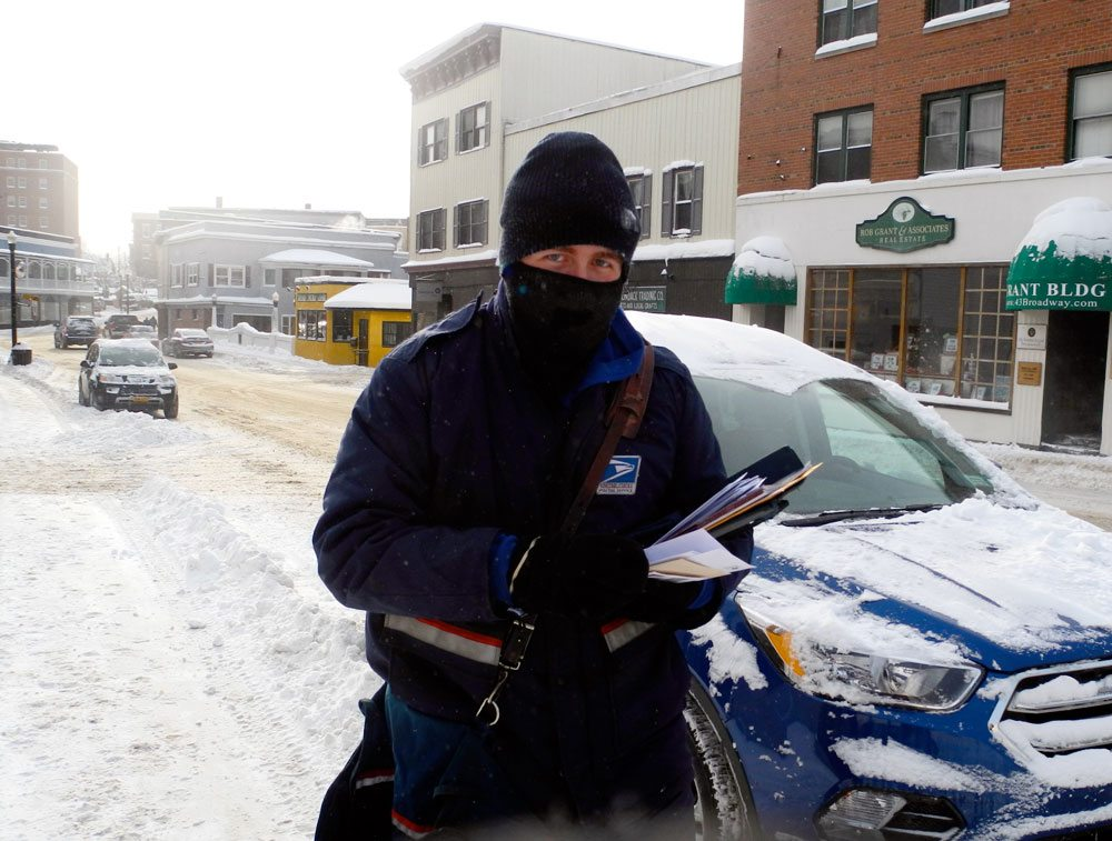 Letter carrier David Lawrence is bundled up to prevent frostbite as he delivers mail on Broadway in downtown Saranac Lake Friday morning, when the temperature is 12 degrees below zero. (Enterprise photo — Peter Crowley)