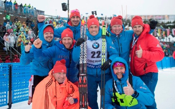 Biathlete Tim Burke, center, celebrates his fourth-place finish in the men's 10-kilometer sprint with U.S. Biathlon coaches and staff today at the BMW IBU World Cup 4 in Oberhof, Germany. (Photo provided — Nordic Focus)