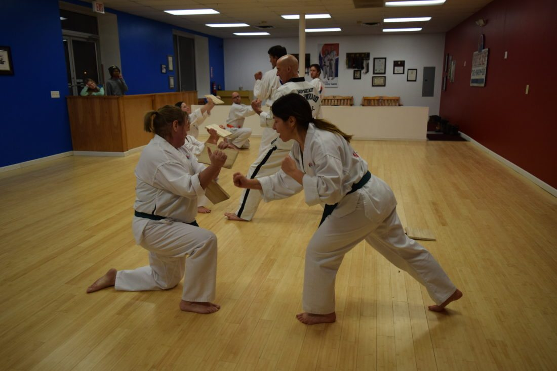 Linda Moore, right, shatters a board held by Lori Keough at Northeast Taekwondo.  (Enterprise photo — Glynis Hart)