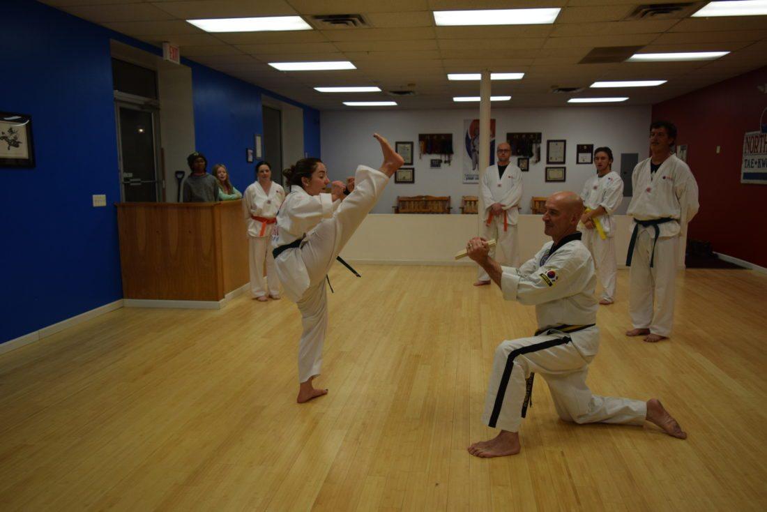 Danielle King smashes a board held by Grandmaster Jon O'Kelly at Northeast Taekwondo in Saranac Lake.  (Enterprise photo —Glynis Hart)