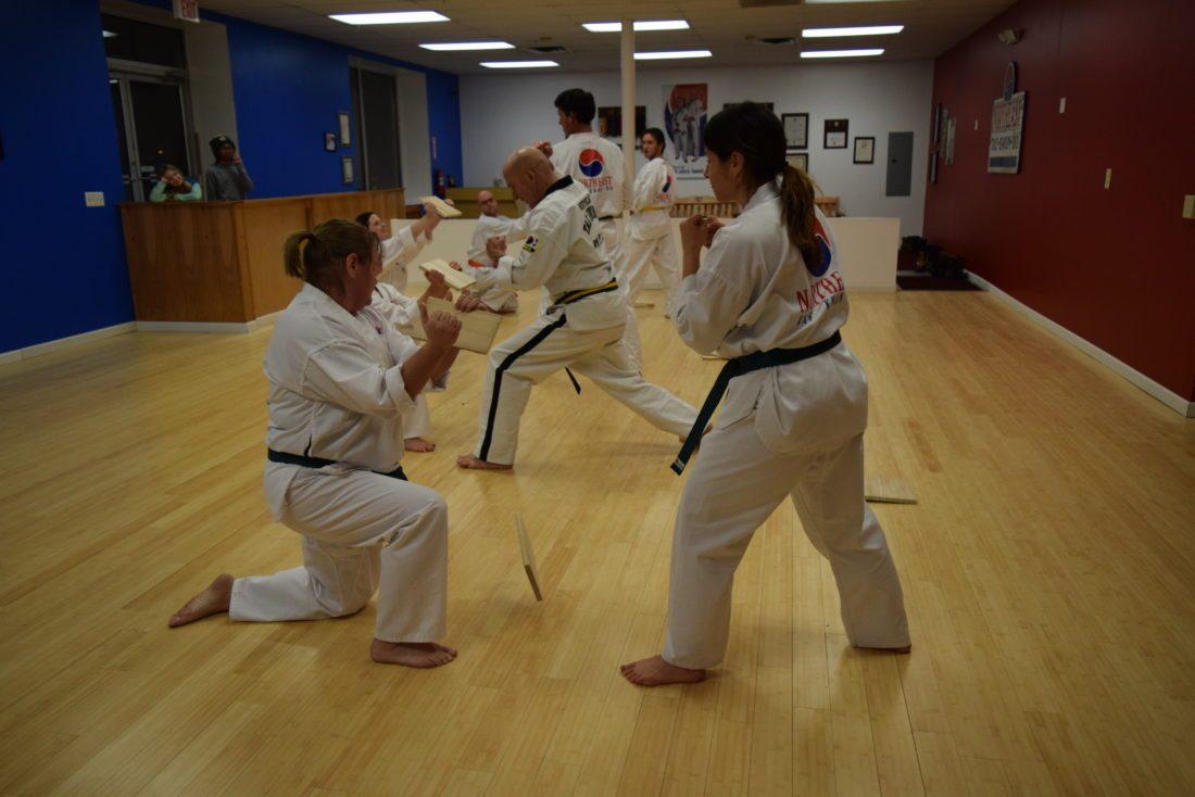 Lori Keough, left, holds a board for Linda Moore to break at Northeast Taekwondo.  (Enterprise photo — Glynis Hart)