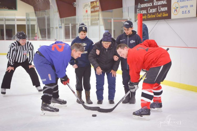 Betty Edwards, Phil Edwards wife, does a ceremonial puck drop at the third annual Phil Edwards Memorial Hockey Tournament with her son Scott Edwards, in red, and Nate Trudeau, in blue. Edward's grandsons, Philip Beaudette, left, and Griffin Shaheen hold Betty's arms. (JMStevens photography)