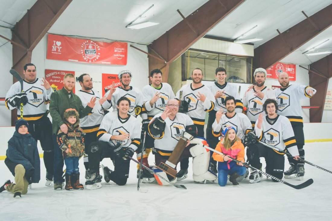 Tessier Paving, the winning team of the  Phil Edwards Memorial Hockey Tournament for the third year in a row, pose with their trophy and children after the  championship game on  Sunday. (JMStevens photography)