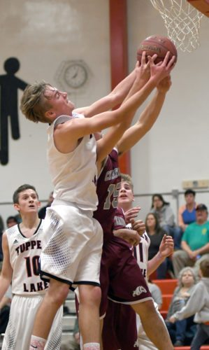 Tupper Lake's Noah Cordes rips down a rebound after winning a battle on the boards with Chateaugay's Kieran Gibson during the second half of Monday's game on the Lumberjacks' court. (Enterprise photo — Lou Reuter)