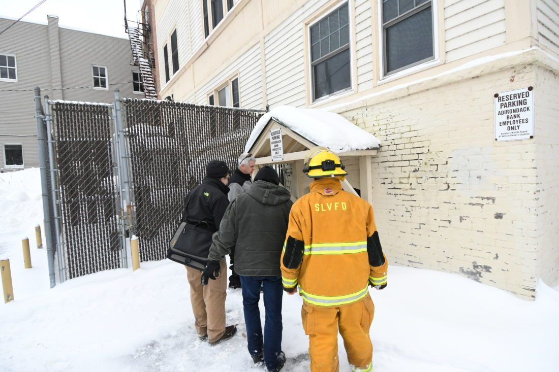 "From left, village of Saranac Lake code enforcement officer Patrick Giblin, fire Chief Brendan Keough and firefighters Ken McLaughlin and Nate Jones gather near the back entrance of the Adirondack Bank's Main Street location Tuesday morning while investigating a burst hot water pipe on the bottom floor. Keough said the water flowed down into the basement and out through a floor drain. ""They have some wet carpets, some ceiling tile down, but relatively speaking, minor damage,"" he said. (Enterprise photo — Lou Reuter)"