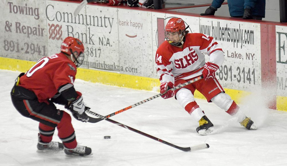 Austen Reyell of Saranac Lake controls the puck in front of Beekmantown's Tyler Baker during the first period of Tuesday's game at the Saranac Lake Civic Center. (Enterprise photo — Lou Reuter)