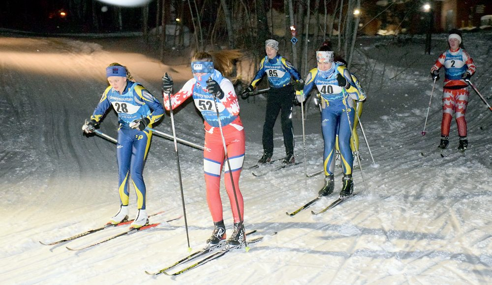 The Saranac Lake and Lake Placid girls varsity nordic skiing teams start a 4.8-kilometer race in light snow Tuesday evening at Dewey Mountain Recreation Center in Saranac Lake. (Enterprise photo — Justin A. Levine)