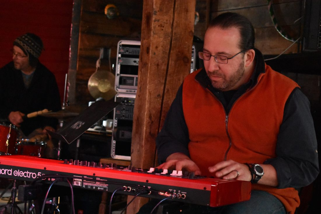 Eric Klotzko doubles as both the sound board operator and a back-up pianist at January Jams. (Enterprise photo —Griffin Kelly)