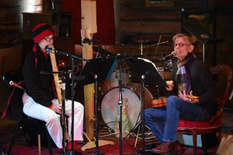 Lynn Waickman (left) plays a recorder while James Coleman plays ukulele and sings at the Upper Jay Art Center's January Jams Sunday, Jan. 7. The large instrument made of plywood standing next to Waickman is also a recorder, one with low octaves close to that of a cello. (Enterprise photo — Griffin Kelly)