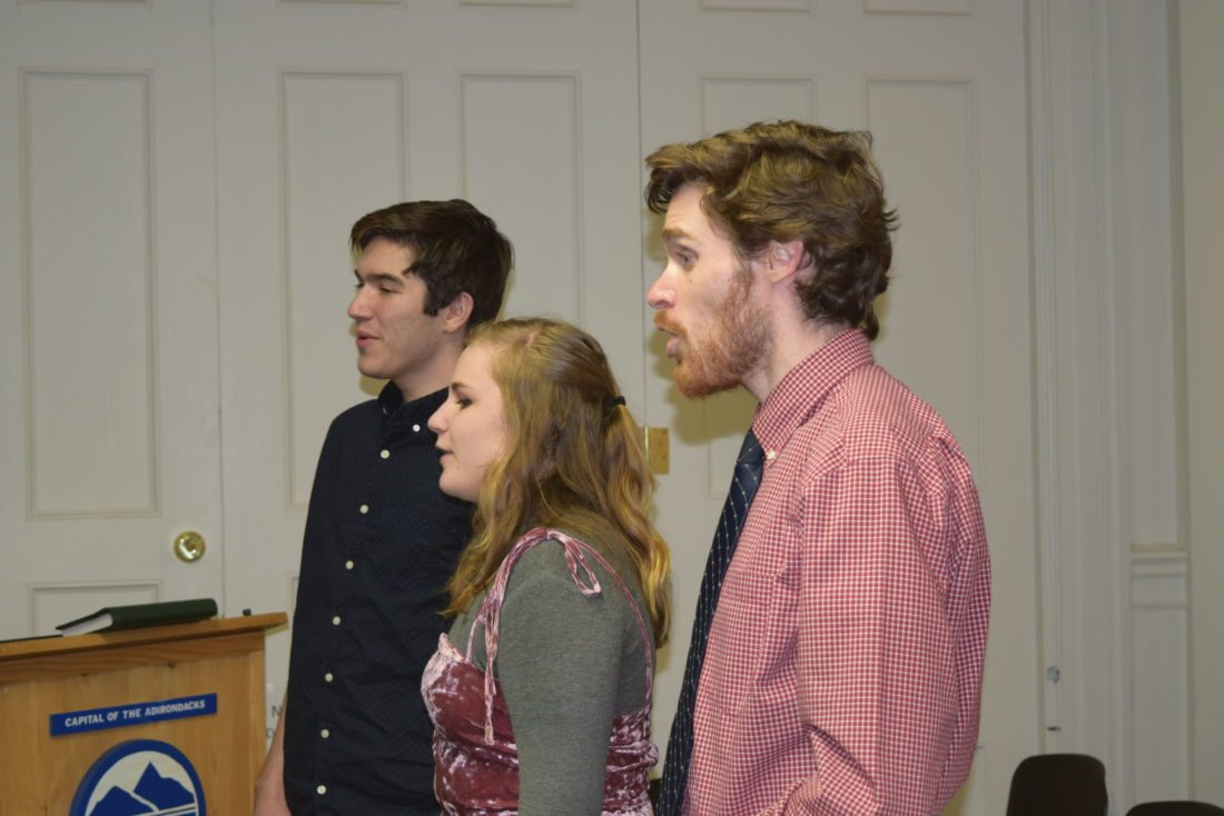 Saranac Lake High School choral director Drew Benware and students Mary Keating and Louis Catania sing a birthday song to Saranac Lake village Trustee Allie Pelletieri. (Enterprise photo — Glynis Hart)