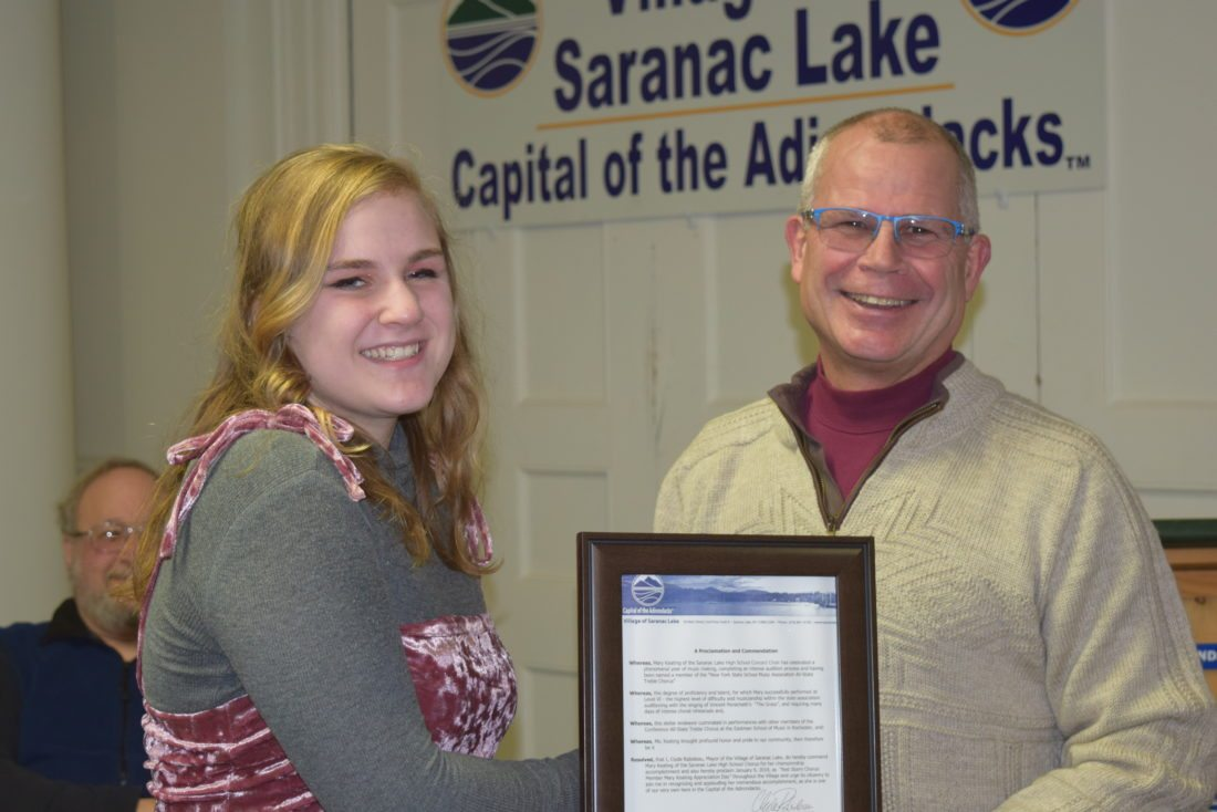 Saranac Lake Mayor Clyde Rabideau presents a plaque of appreciation to high school junior Mary Keating for her achievement in being invited to the All-State NYSSMA Chorus held in Rochester in November. (Enterprise photo — Glynis Hart)