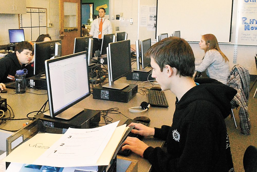 Lumberjack Lyre advisor Zachary Arthur oversees production of the February issue Wednesday at Tupper Lake middle-high school. (Enterprise photo — Aaron Cerbone)