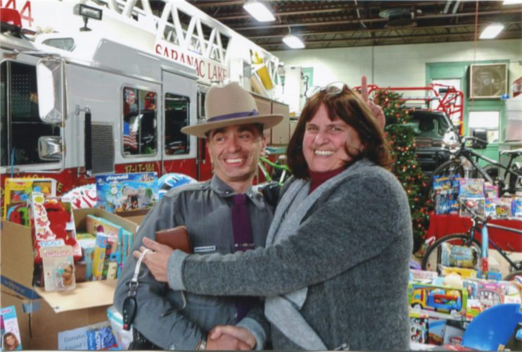 State Trooper James D'Ambro concedes to Found Caravan Corvette Club member Joanne Bevilacqua that her group donated more Christmas gifts than his in the Saranac Lake Volunteer Fire Department Toy Drive for Holiday Helpers Nov. 25 at the firehouse. (Photo provided — Patti Ploof)