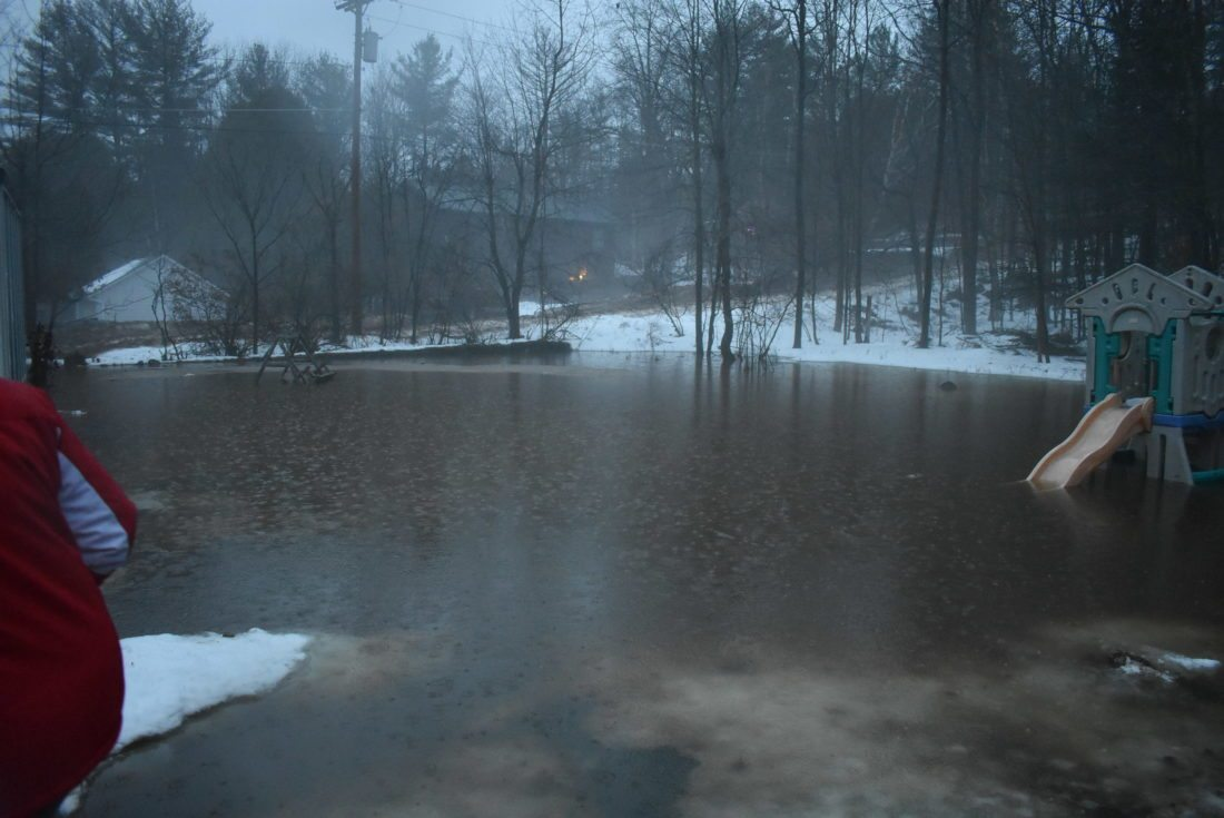 The backyard of Rip and Shirley Allen on Kiwassa Road in Saranac Lake is flooded Friday afternoon amid heavy rains and temperatures in the 50s. (Enterprise photo — Griffin Kelly)