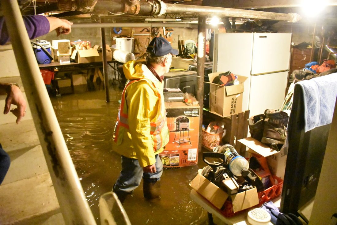 Upper left, Shirley Allen of Saranac Lake directs a member of the village fire department through her flooded basement Friday evening. Her fridge and furnace took on more than a foot of water. (Enterprise photo — Griffin Kelly)