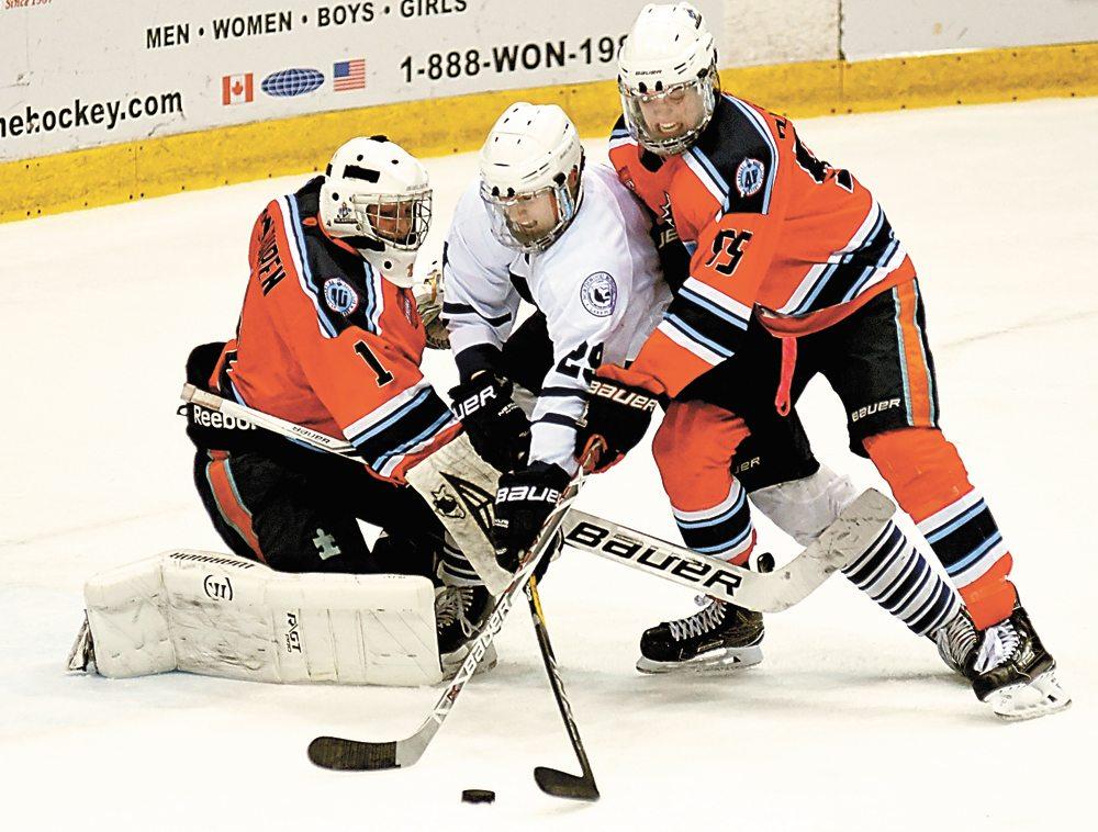 Aleksei Rutkovskii of Northwood attempts to skate with the puck between Islanders goaltender Grant Van Buren and defender Jacob Rodrigue.  (Enterprise photo — Lou Reuter)