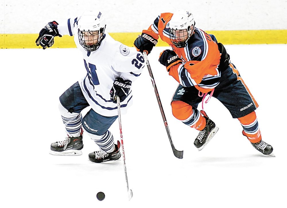 Weston Batt of Northwood heads for the puck in front of Liam Lyons of the Islanders late in Friday's game at the Olympic Center inLake Placid. Batt scored twice to lead the Huskies to a 5-2 triumph. (Enterprise photo — Lou Reuter)