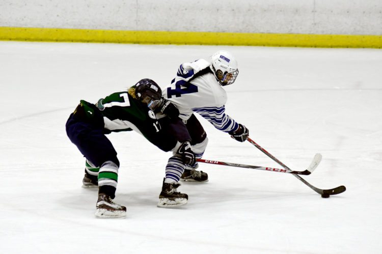 Sierra Benjamin of Northwood skates with the puck while attempting to break away from Kyla Bent of Rothesay Netherwood during Sunday's game at the Olympic Center's 1932 Rink. The Huskies will play in today's girls division championship game of the 39th annual Northwood Hockey Invitational after posting a win and two ties over the weekend in opening-round play. The final will be against the U16 Selects and begins at 2:30 p.m.