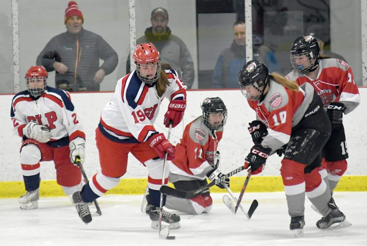 Katelyn Gay of Saranac Lake Placid skates with the puck while Bailey Carter of Beekmantown closes in during action Wednesday in Saranac Lake. Also pictured are Faith Fell of SLP and Eagles Ireland Preston (11) and Leah Coulombe. (Enterprise photo — Lou Reuter)
