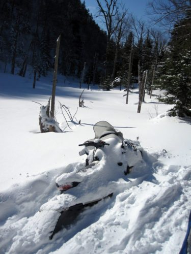 A riderless snowmobile is stuck in snow on the Old Mountain Road trail in February 2010. (Photo provided — Andy Walkow)