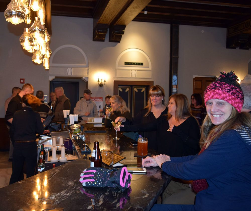 Sally Muldowney, right, and other Saranac Lakers gravitate to the bar in the Great Hall as the Hotel Saranac reopens Thursday afternoon.  (Enterprise photo — Glynis Hart)