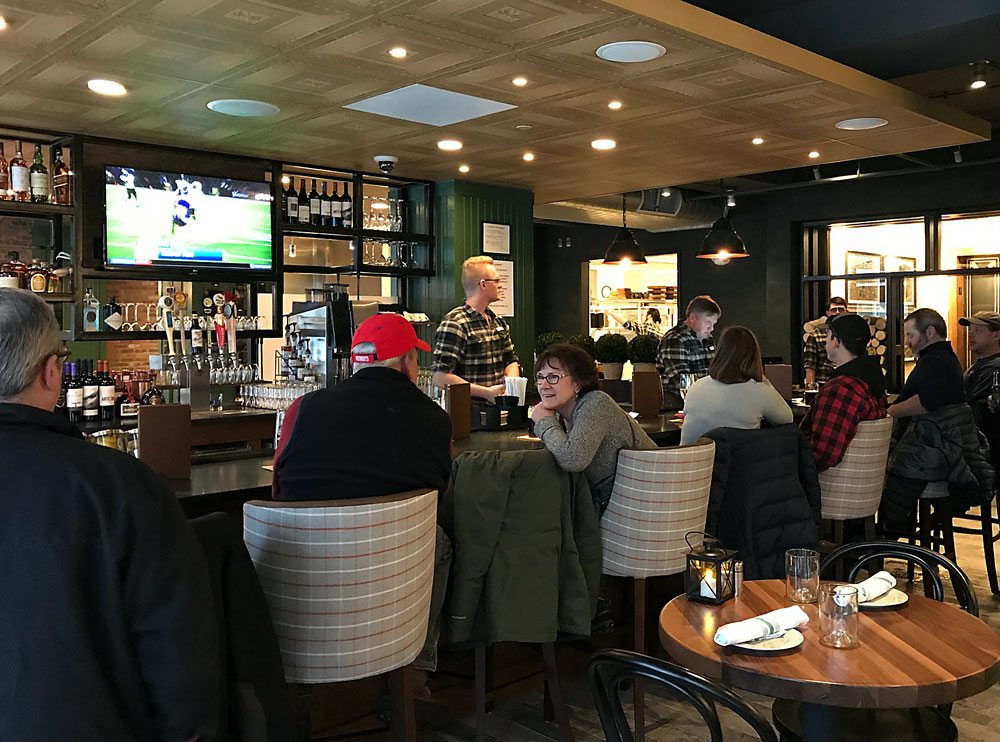 Saranac Lakers chat and watch a game on television at the Hotel Saranac's Camp Fire bar, opened for the first time Thursday afternoon. (Enterprise photo — Catherine Moore)