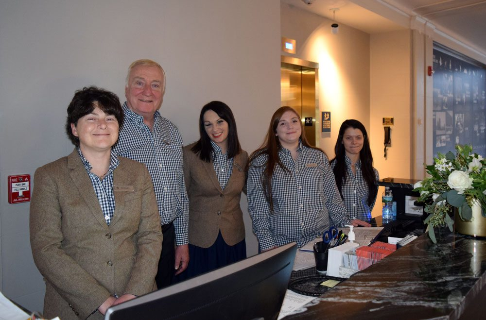 Hotel Saranac staff members Beatrice, David, Alex, Miranda, and Susan greet guests at the front desk Thursday. (Enterprise photo — Glynis Hart)