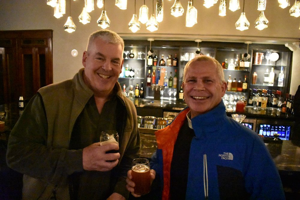 New York State Police officer Mike Ryan, left, and Saranac Lake village Mayor Clyde Rabideau drink beers at the grand reopening of the Hotel Saranac Thursday. (Enterprise photo — Griffin Kelly)