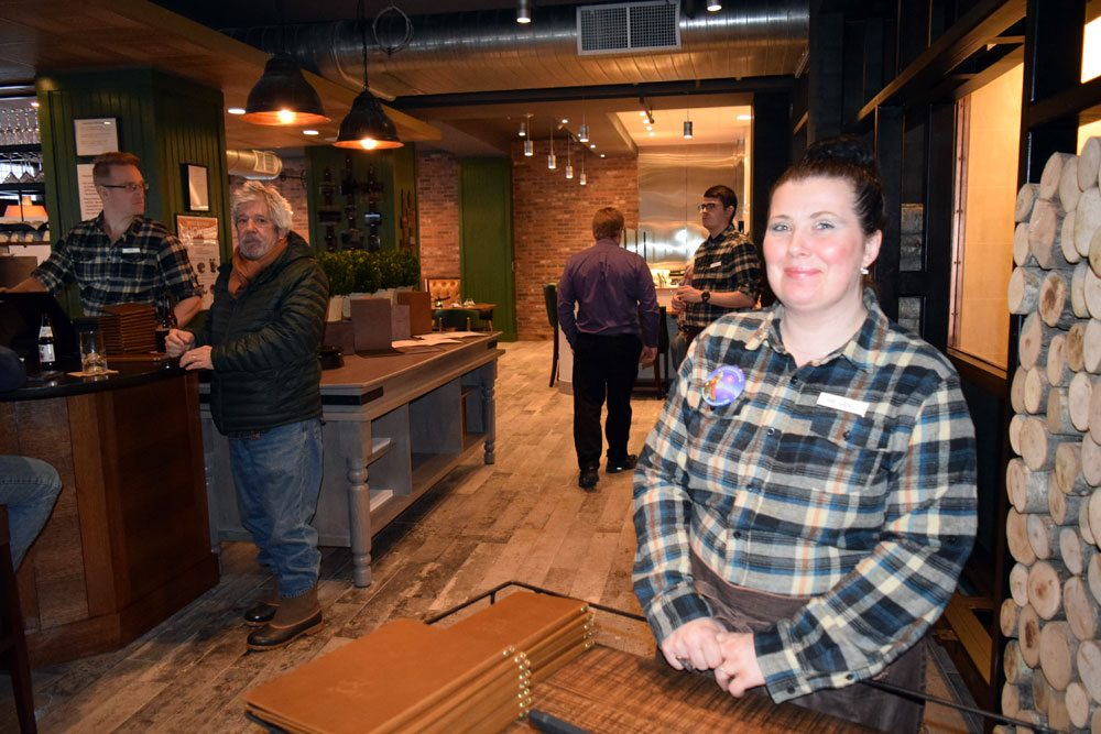 Hotel Saranac staff member Megan Klovus welcomes guests to Camp Fire, the restaurant, as the hotel reopens Thursday. (Enterprise photo — Glynis Hart)
