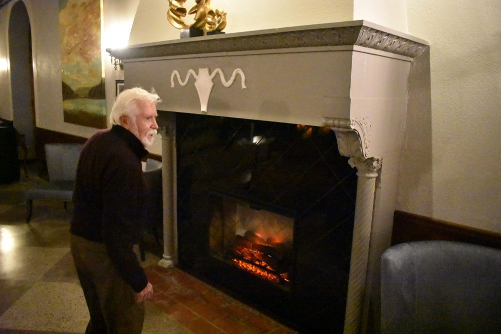 Town of Harrietstown Councilman and former Saranac Lake Mayor Howard Riley stands in front of the fireplace at the Great Hall Bar at the Hotel Saranac during its reopening Thursday. (Enterprise photo — Griffin Kelly)