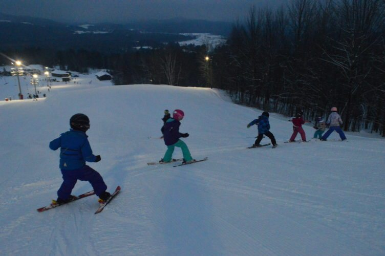 "Erica Swirsky, left, a 17-year-old from Gabriels, teaches a group of first- and second-graders to ski at Mount Pisgah in Saranac Lake Friday evening. The lessons, organized through the Saranac Lake Ski Club, have high school students pass on the ski skills they grew up learning. ""To have another generation know how to do it, it's incredible,"" Swirsky said. ""I think it's one of those things you should just know how to do."" (Enterprise photo — Aaron Cerbone)"