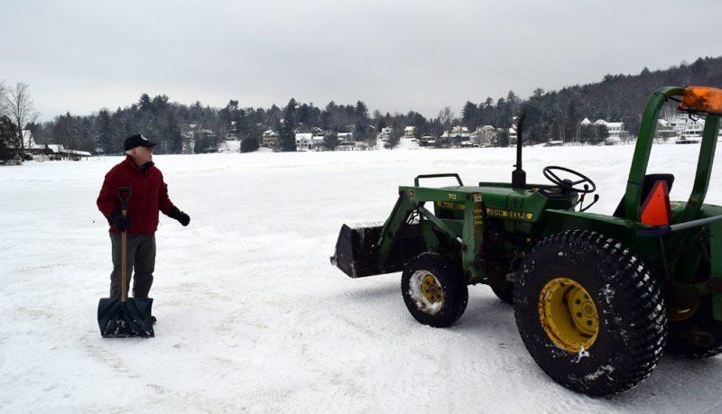Dean Baker supervises clearing slush off the ice Friday. (Enterprise photo — Glynis Hart)
