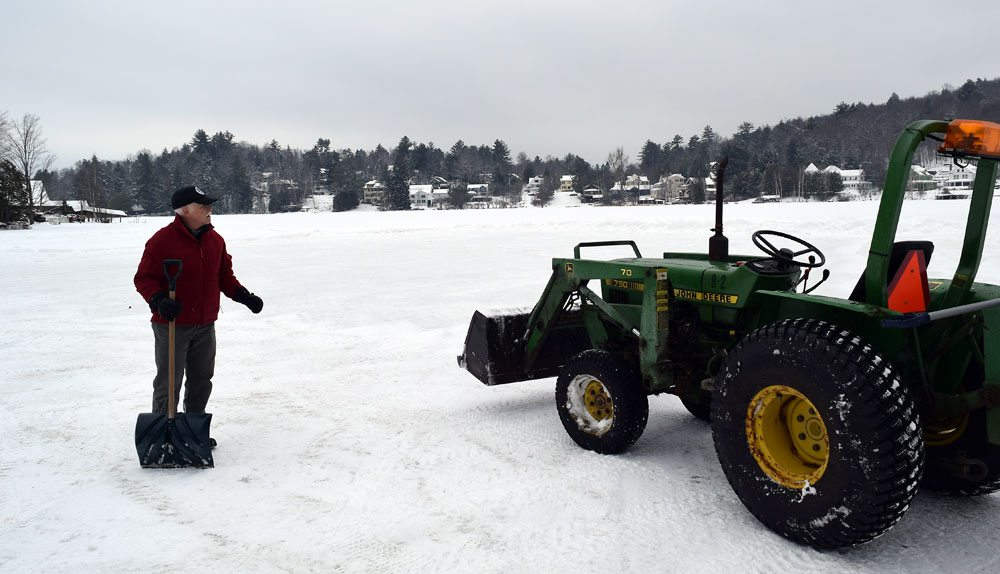 Dean Baker supervises clearing slush off the ice Friday. (Enterprise photo — Glynis Hart)