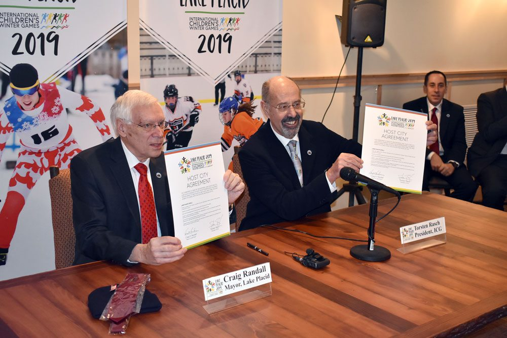 Lake Placid village Mayor Craig Randall, left, and International Children's Games President Torsten Rasch sign contracts Tuesday at the Olympic Jumping Complex's Intervale base lodge, making Lake Placid the site of the 2019 winter International Children's Games. (Enterprise photo — Griffin Kelly)