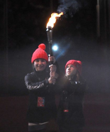 Saranac Lake Middle Schoolers Emma Wood, left, and Ruby Smith carry the Empire State Winter Games torch across the ice before handing it off for the lighting of the cauldron during the opening ceremonies in February 2016 at the Olympic Center in Lake Placid. (Enterprise photo — Lou Reuter)