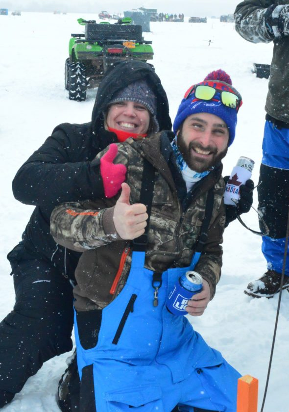Andrea LaMere and Christopher Duhaime sit by one of Duhaime's holes with a triggered tip-up flag at the Northern Challenge Fishing Derby in Tupper Lake. Though the line was empty, the party carried on, everyone knowing there was more time to pull up a prize-winning pike. (Enterprise photo — Aaron Cerbone)
