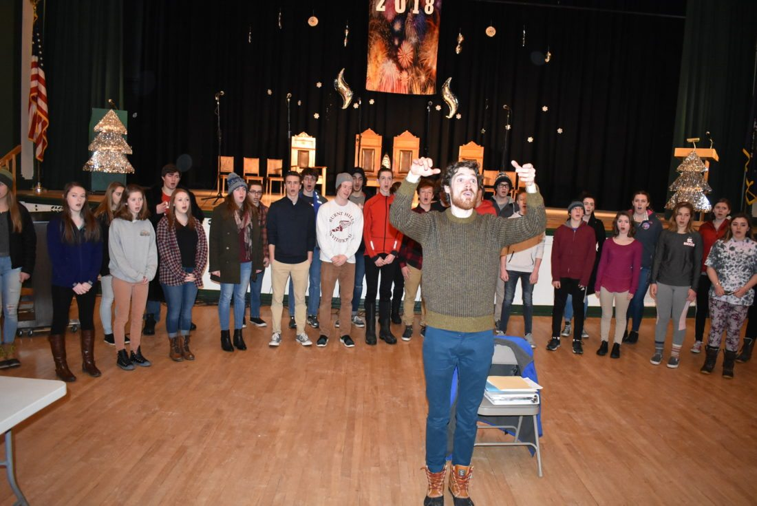 Drew Benware, director of choral activities at Saranac Lake High School, conducts the boys and girls vocal ensembles at a practice Sunday for the Rotary Club Variety Show. (Enterprise photo — Griffin Kelly)