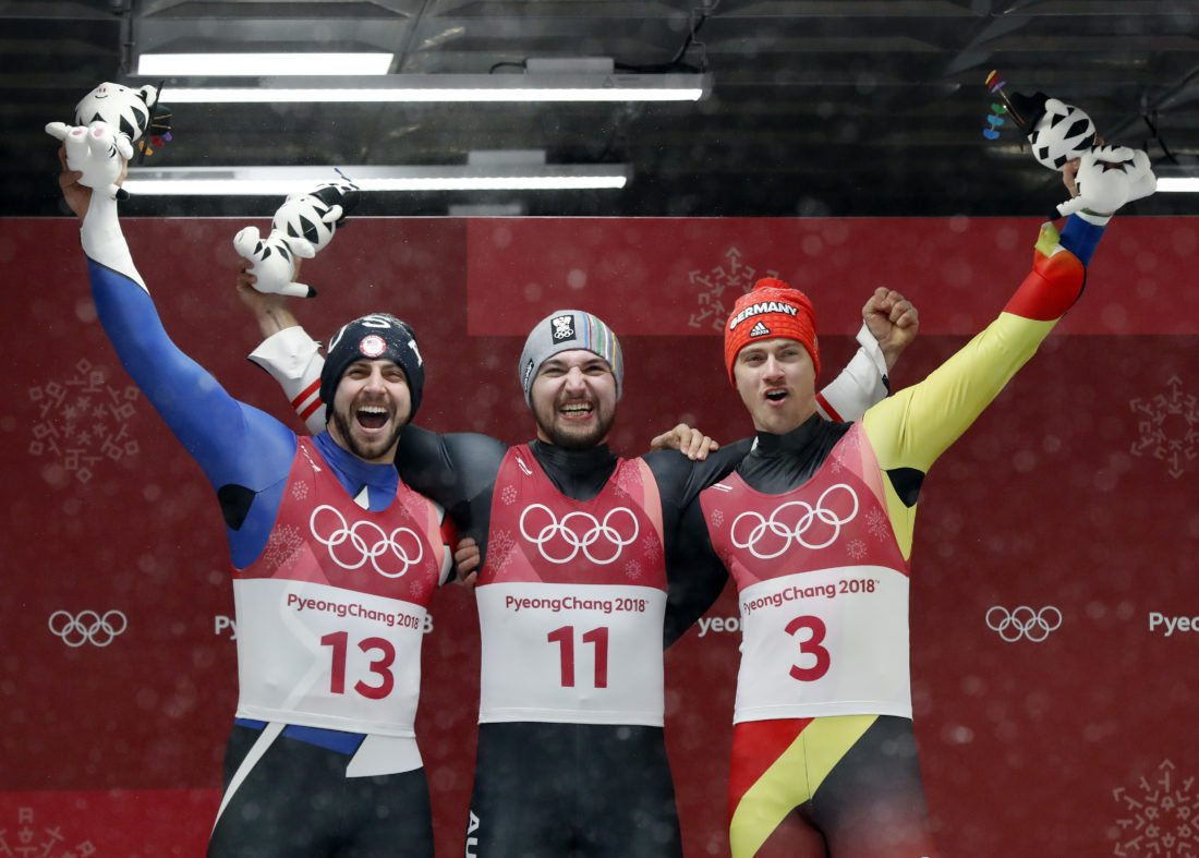 Silver medalist Chris Mazdzer, left, gold medalist David Gleirscher of Austria, center, and bronze medalist Johannes Ludwig of Germany smile during the winners ceremony after the men's luge competition Sunday at the 2018 Winter Olympics in Pyeongchang, South Korea. (AP Photo/Andy Wong)