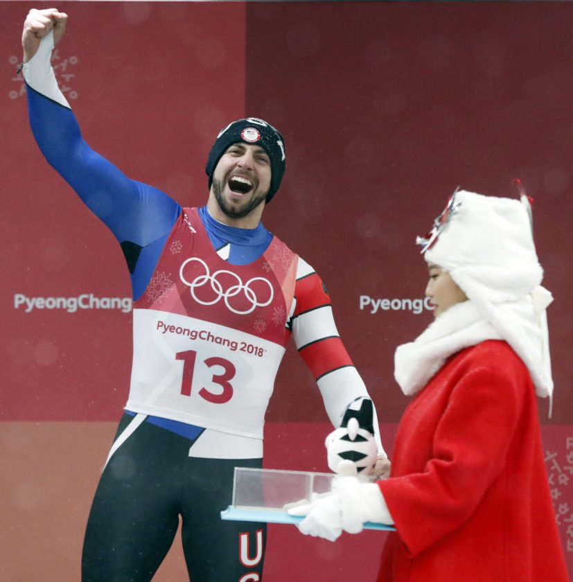 Chris Mazdzer shouts after getting a toy tiger for taking the silver medal during the winner's ceremony of the men's luge competition Sunday at the 2018 Winter Olympics in Pyeongchang, South Korea. (AP Photo/Andy Wong)