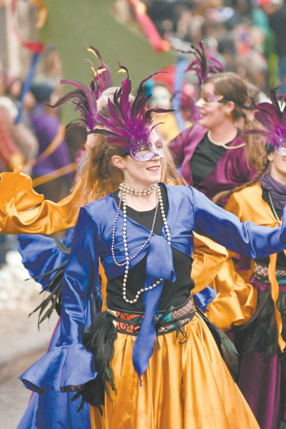 Tammy Loewy of the colorfully-clad Soma Beats dance group dances on Main Street during Saturday's Saranac Lake Winter Carnival gala parade. (Enterprise photo — Lou Reuter)