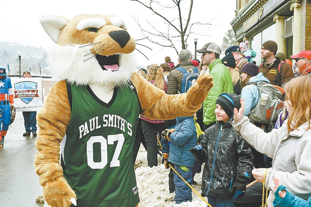 Paul Smith's College's mascot, the Bobcat, high-fives a youngster during the Saranac Lake Winter Carnival Parade Saturday.  (Enterprise photo — Glynis Hart)