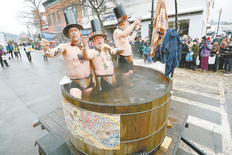 Joe Dadey, Bob Seidenstein and Jack Drury of the Brothers of the Bush hot-tub their way through the village during Saturday's Winter Carnival Gala Parade. (Enterprise photo — Lou Reuter)