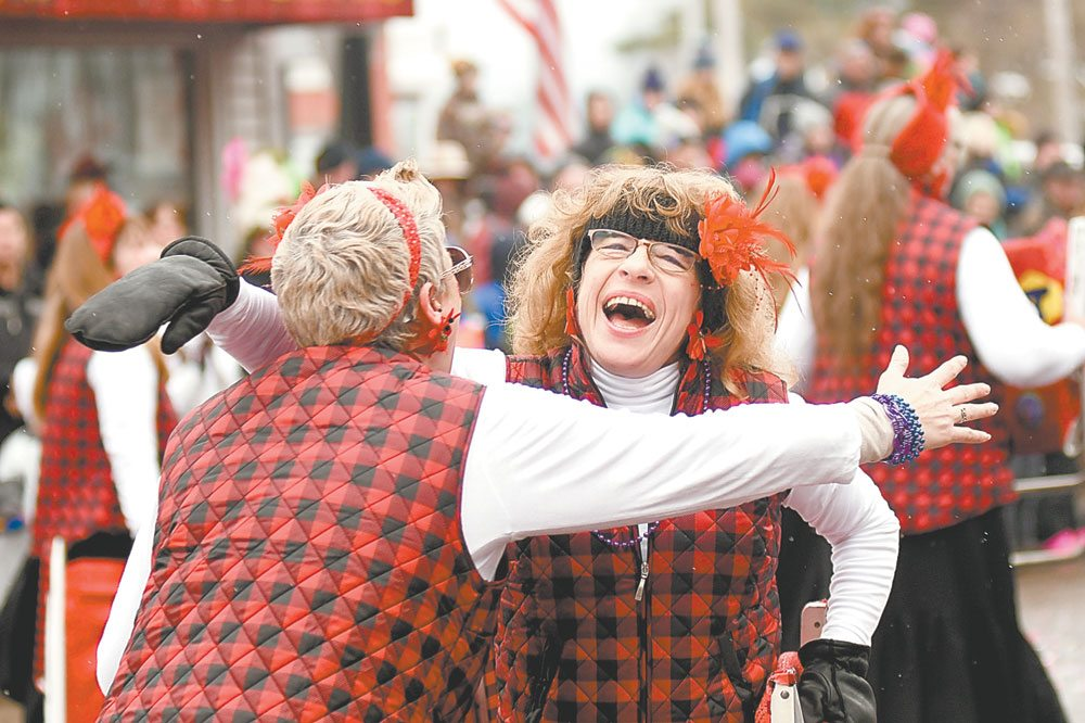 Brandy Clark, left, is greeted by fellow Lawn Chair Lady and this year's Winter Carnival Queen Nancy LaBombard in front at the end of the gala parade route on Saturday. (Enterprise photo — Lou Reuter)