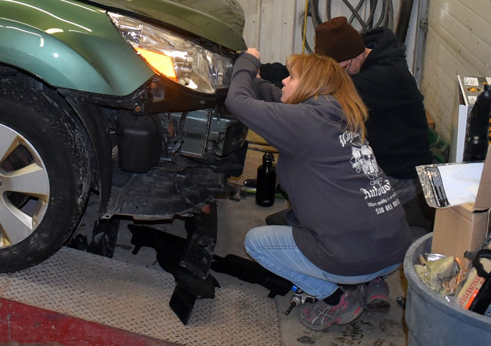 Nicole Darrah and Kurt Casler try to fix a busted hood latch on a car at Wayne Darrah Auto Body, the family-run shop in Saranac Lake where Nicole's brother Patrick Darrah worked for many years before starting his country music career. (Enterprise photo — Griffin Kelly)