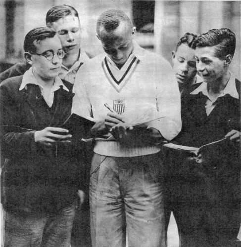 Jesse Owens signing autographs for British youths when the U.S. team was competing in London in the 1948 Olympic Summer games.