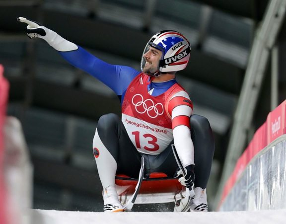 Chris Mazdzer of United States brakes in the finish area after his first luge run at the 2018 Winter Olympics in Pyeongchang, South Korea, Saturday, Feb. 10, 2018. (AP Photo/Michael Sohn)