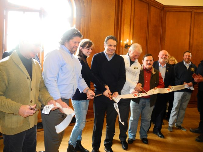 From left, Saranac Lake Mayor Clyde Rabideau, Hotel Saranac co-owner Fred Roedel III, Maria Kennedy Cuomo, Clarkson University President Tony Collins, North Country Chamber of Commerce director Garry Douglas, Franklin County board Chairman Don Dabiew and others cut a ribbon for the Hotel Saranac in its Ballroom Saturday in Saranac Lake. (Enterprise photo - Peter Crowley)