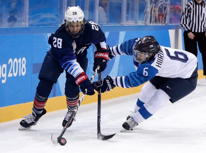 Amanda Kessel, left, and Jenni Hiirikoski, of Finland, battle for the puck during the second period of Monday's semifinal game in Gangneung, South Korea. (AP photo — Matt Slocum)