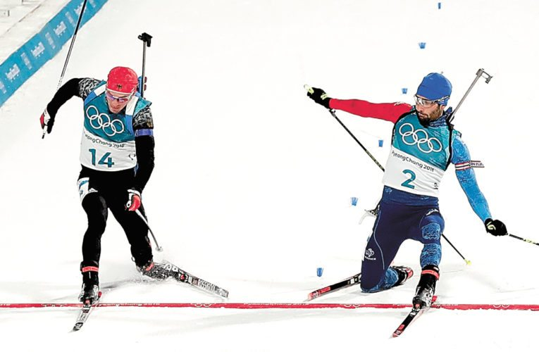Germany's Simon Schempp, left, and Martin Fourcade, of France, cross the finish line during the men's 15-kilometer mass start biathlon Sunday at the 2018 Winter Olympics in Pyeongchang, South Korea. Fourcade was awarded the gold medal after a photo finish review.  (AP photo — Andrew Medichini)