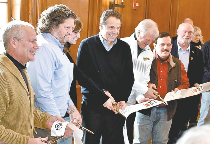 From left, Hamilton County Board of Supervisors Chairman Bill Farber, Saranac Lake Mayor Clyde Rabideau, Hotel Saranac co-owner Fred Roedel III, Mariah Kennedy Cuomo, New York Gov. Andrew Cuomo, Clarkson University President Tony Collins, North Country Chamber of Commerce President/CEO Garry Douglas, Franklin County Board of Supervisors Chairman Don Dabiew and others cut a ribbon for the Hotel Saranac in its Ballroom Saturday in Saranac Lake. (Enterprise photo — Griffin Kelly)